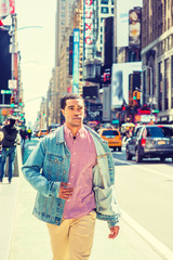 Young African American Man traveling in crowded Times Square, New York, wearing Denim jacket unbuttoned, red, white patterned shirt, yellowish brown pants, walking. High Buildings, cars on background.