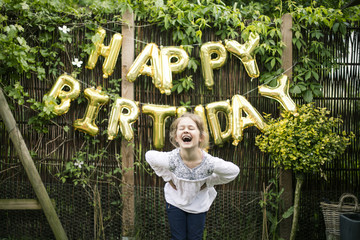 Portrait of laughing girl in the garden with decoration for Birthday Party in the background