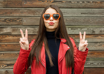 Beautiful smiling brunette woman in sunglasses over wooden background. Street fashion. Outdoors.