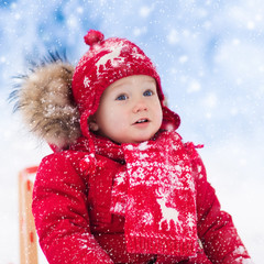 Kids play in snow. Winter sleigh ride for children