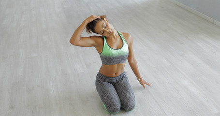 Young confident sportive woman in special outfit sitting on floor of studio and bending neck on side warming up muscles.