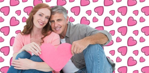 Composite image of casual couple holding pink heart