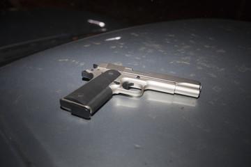 Pistole auf Autodach Schnappschuss