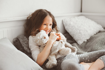 happy kid girl playing with teddy bears in her room, sitting on bed in pajama