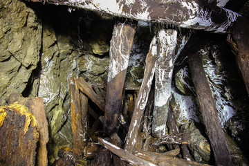 Underground abandoned ore mine shaft tunnel gallery passage with wooden timbering