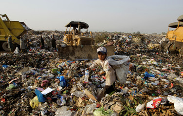 A seven year old boy collects recyclables after school at the landfill in Islamabad