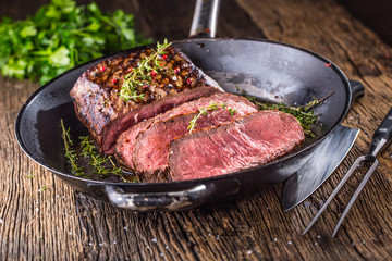 Beef steak. Juicy medium Rib Eye steak slices in pan on wooden board with fork and knife herbs spices and salt