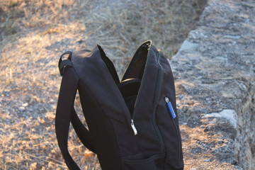 backpack on the edge of a cliff with ocean on the background at a autumn evening during a hiking session