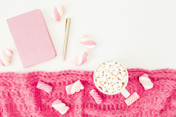 Feminine concept of marshmallow with cappuccino mug, cloth, pen and notebook on white background. Flat lay, top view. Female desk