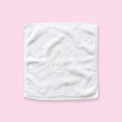 White cotton towel mock up template square size isolated on pastel pink background with clipping path, flat lay top view