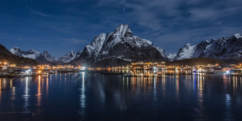Village on the Lofoten Islands at night, in the foreground the sea in the background the mountains