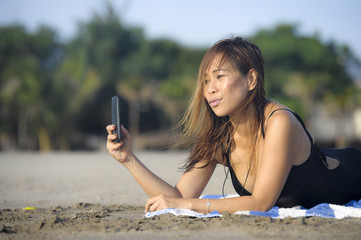 happy Asian woman using mobile phone taking selfie portrait photo having fun relaxed