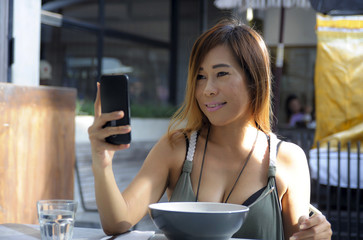 happy Asian woman using mobile phone taking selfie portrait photo having fun relaxed sitting at coffee shop