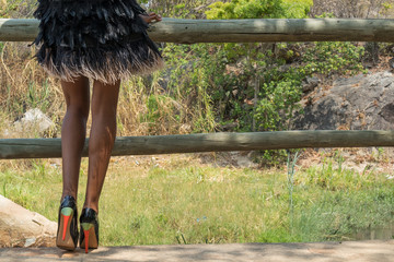African girl legs with fashion shoes, vegetation in background.