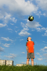 A boy looks at the ball in the air