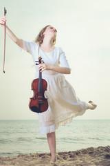Woman on beach near sea holding violin