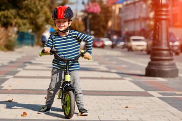 Happy boy ride a bicycle in city park