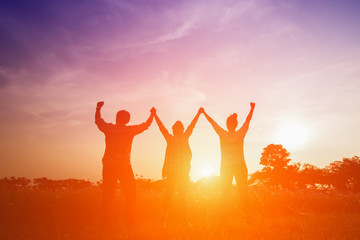 Silhouette image of happy family making high hands in sunset