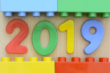 Close up of year 2019 in colorful plastic numbers surrounded by plastic toy blocks