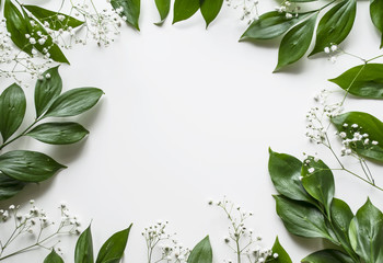 Creative layout of foliage on a white background with space for text. White gypsophila. Frame of leaves and flowers. Floral background. View from above.