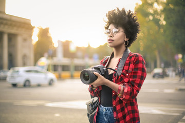 Beautiful woman taking photos in a city