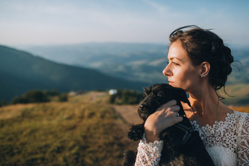 Bride stands with black puppy on a green hill