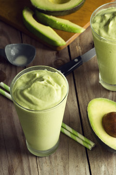 Two Glasses of Avocado Shake or Smoothie with Ingredients on Wooden Table