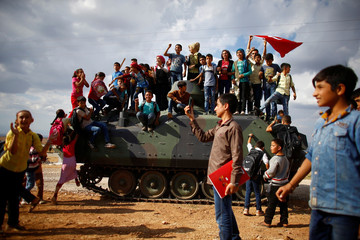 Children stand on top of Turkish army vehicle on the Turkish-Syrian border line in Reyhanli