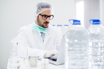 Young handsome scientist with glasses working on laptop in the laboratory.