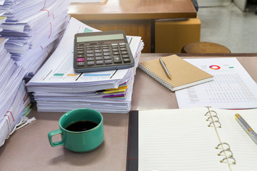 Close up of a cup of coffee and business documents on desk
