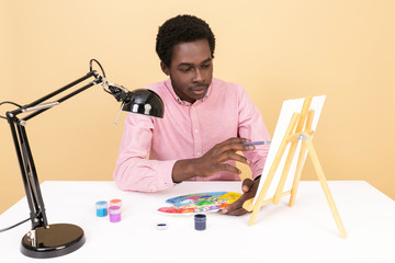 Black man painting on canvas in his office