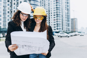Two young pretty business women industrial engineers in construction helmets on a glass building background. Construction plan, architect, designer, successful