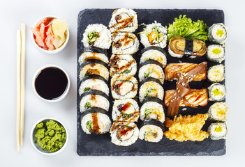 Sushi set poured with soy sauce, wasabi and ginger on white table