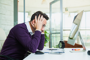 Tired businessman student hold his head. Upset office worker nervous angry hipster man at light office with computer monitor. Diappointed with job done