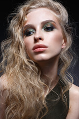 Young girl with curls and bright creative make-up. Beautiful model in earrings and green top. Beauty of the face. Photo is taken in the studio. evening image.