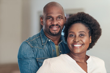 Content African couple smiling and standing together at home