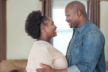 Affectionate African couple standing at home looking at each other
