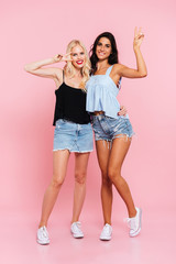 Full length image of two cheerful women in summer clothes