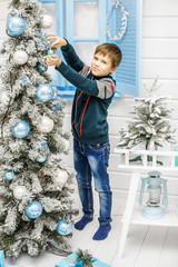The child adorns the Christmas tree. The boy in the sweater. Concept New Year, Merry Christmas, holiday, winter.