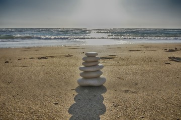 Stones balance and wellness retro spa concept, inspiration, zen-like and well being tranquil composition. Close-up of white pebbles stack over blue sea Fotomurales