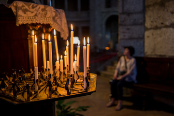 candles and woman in church in Saint Ambrogio Church in Milan