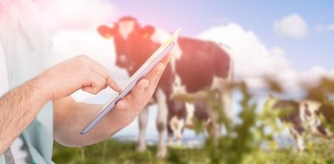 Composite image of man using tablet pc against rural scene