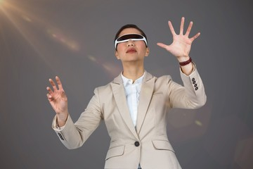 Composite image of businesswoman wearing virtual video glasses