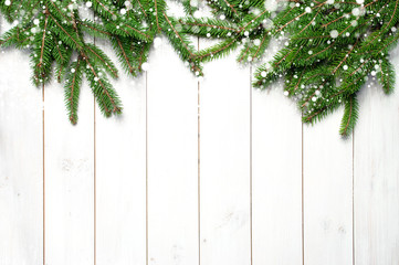 Christmas snow-covered branches on a white wooden background. New Year's background, holiday, christmas, snow, winter, green branches top view with copy space.