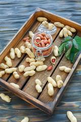 Glass jar with peeled peanuts.