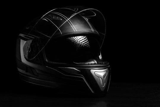 A black motorcycle helmet on dark background.