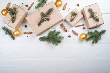 Christmas background with gift boxes wrapped in kraft paper, fir tree branches, golden glass balls, pine cones, cinnamon and stars anise on white wooden background, free space. Flat lay, top view