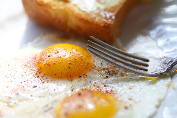 fried eggs with smoked paprika and black pepper with fork and buttered toast