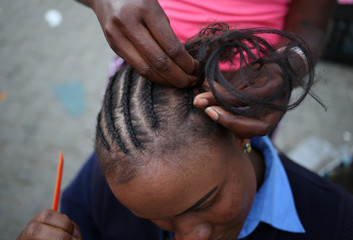 A customer has her hair braided on a roadside shop in Soweto