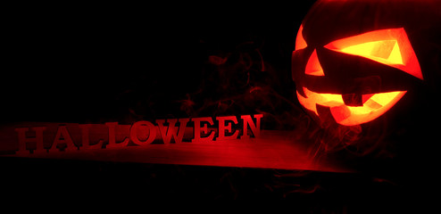 Halloween concept. Scary spooky pumpkin with Halloween inscription, with a hot fire glow and smoke, a poster for a party